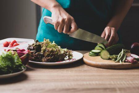 Woman cutting vegetables preparing for making vegan salad