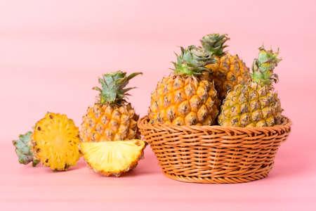Fresh pineapple fruit in a basket on pastel pink background, Tropical fruit Standard-Bild