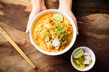 Northern Thai food (Khao Soi), Spicy curry noodles soup with chicken in a bowl eating with pickled mustard, shallots and lime Reklamní fotografie