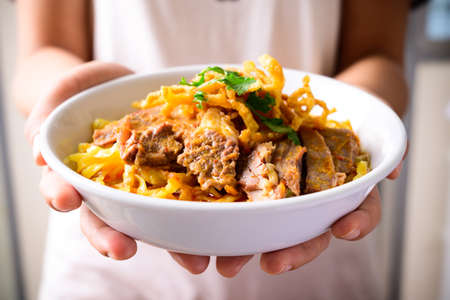 Northern Thai food (Khao Soi), Spicy curry noodles soup with beef in a bowl holding by hand