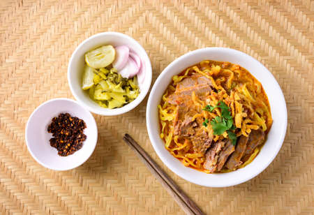 Northern Thai food (Khao Soi), Spicy curry noodles soup with beef eating with pickled mustard, shallot, lime and ground chili fried in oil Banco de Imagens