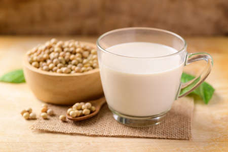 Soy milk in the glass and soy beans on wooden background