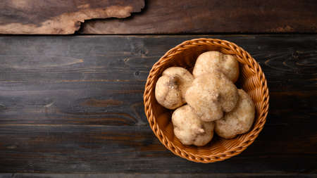 Fresh jicama or yam in a basket on wooden background,Jicama can be eaten raw or cooked, The taste are crisp, juicy, moist, and slightly sweet 版權商用圖片
