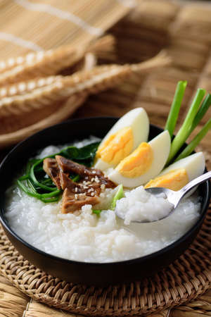 Asian breakfast food, Rice soup with boiled egg, grilled mushroom and spinach in a bowl