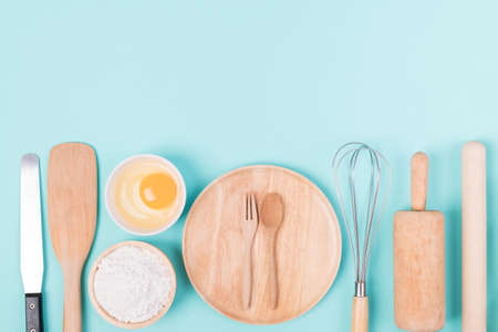 Kitchen utensils and food ingredients for bakery cooking on color background, Top view