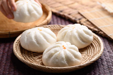 Steamed buns stuffed with minced pork holding by hand, Asian food