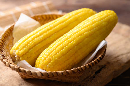 Sweet corn cob in a bamboo basket on wooden background Stock fotó