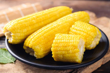Sweet corn cob on black plate with wooden background