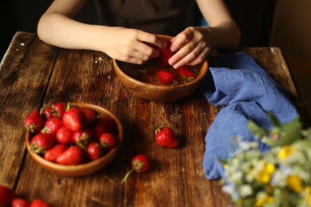 A lot of ripe red strawberries in children's palms. The child washes strawberries in clean water.