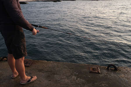 The man is fishing in the sea. Sports fishing. Boat trip, tourist activities at sea. 版權商用圖片