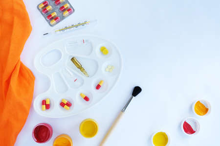 On a white background, a palette for paints and in it are pills, ampoules and a thermometer, next to it there are paints with a brush. Stock fotó