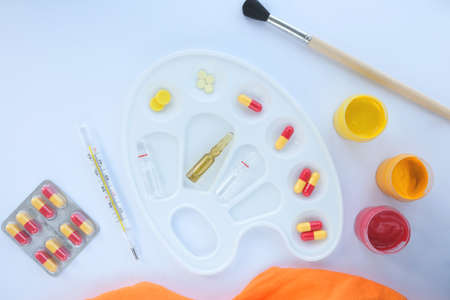 On a white background, a palette for paints and in it are pills, ampoules and a thermometer, next to it there are paints with a brush.