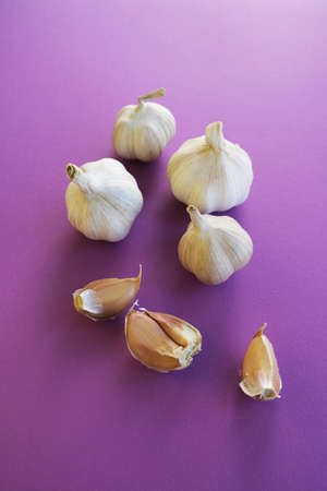 Set of fresh garlic cloves on a lilac background. Place for text. Фото со стока