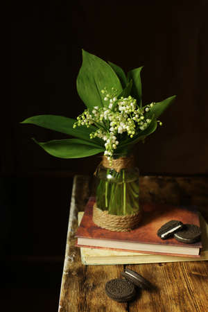 On a wooden table there are chocolate chip cookies, and in a vase there is a bouquet of white lilies of the valley. Фото со стока