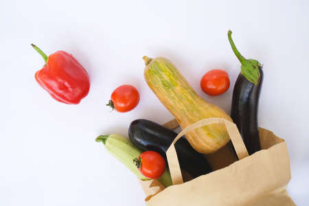 Healthy food background. Vegetables in paper bag on white, copy space, banner. Shopping grocery supermarket and pure vegan food concept.