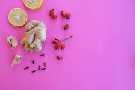 Ginger, lemon, clove, rose hips and garlic on a raspberry background. Ingredients to boost immunity.