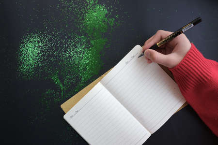 Festive green decorations, hand writes in a notebook, on a black table