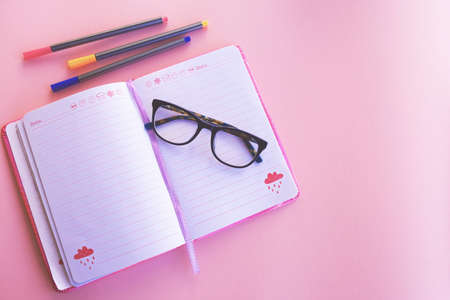 Flat composition with notebooks, colored pens and glasses, pink background. Stock fotó