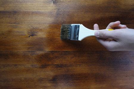 Flat paintbrush paints wood background. Preparing for the summer season. Home repairs.