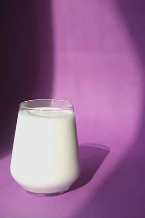 Fresh and cold milk on a purple background. Light from the window. Stock fotó