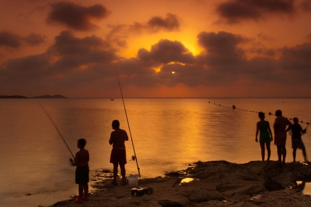In holiday the family goes together to fish at the beach photo