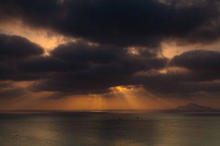 In a summer afternoon the sun tries to break the dark clouds photo