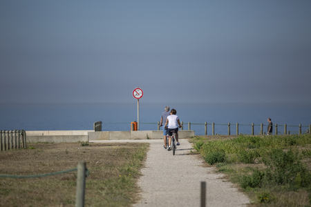 Back view of middle-aged couple, cycling on the eco pedestrian  bike path, near the sea, Portugal Editorial