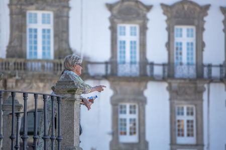 OportoPortugal - 10022018 : View at the Women talking on balcony on Porto Cathedral , Sé do Porto, episcopal palace of Porto as background