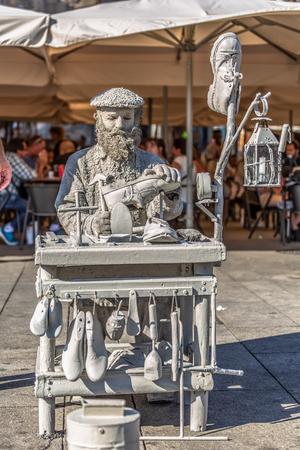 PortoPortugal - 10 04 2018: View of statue man, doing shoemaker acting on the street, Porto city, Portugal...
