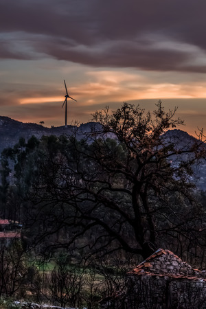 View of a rural scenario on sunset, wind turbine on top of mountains and dramatic sunset sky as background, in Portugal... Imagens