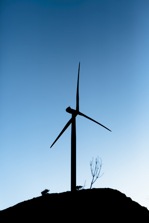 Silhouette view of a wind turbine on top of mountains, cold version sunset sky, in Portugal
