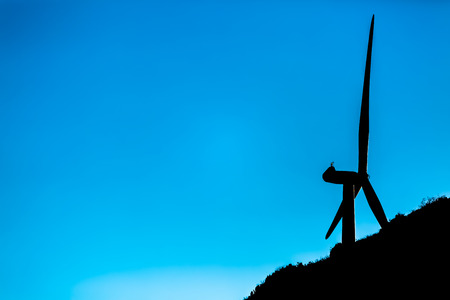 Silhouette view of a wind turbines on top of mountains, cold version sunset sky, in Portugal 免版税图像