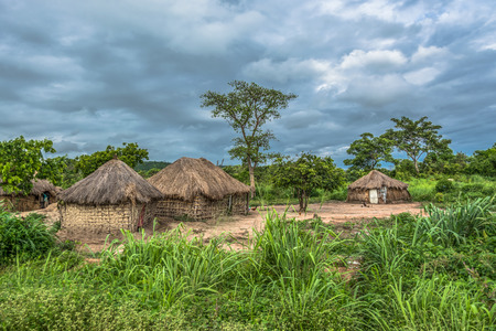 View of traditional village, house thatched with roof and terracotta and straw walls, cloudy sky as background Reklamní fotografie