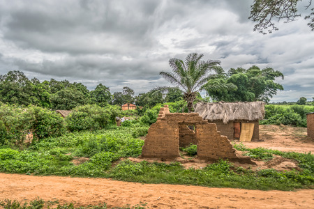 View of traditional village, terracotta ruin wall and thatched and zinc sheet on roof houses and terracotta brick walls, cloudy sky as background, in Angola Фото со стока