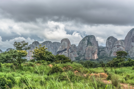 View of a tropical landscape, with forest and mountains Pungo Andongo, Pedras Negras , black stones, huge geologic rock elements, cloudy sky as background, in Malange, Angola