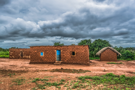 View of traditional village, thatched houses with roof and terracotta brick walls, cloudy sky as background, in Angola