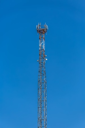 View of a tower with telecommunications antennas, details of the metallic structure and equipment, blue sky as background