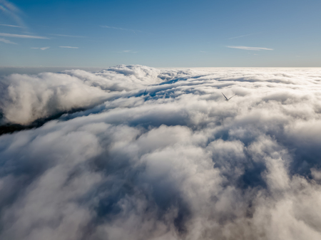View of a drone above the fog, wind turbines with fog and blue sky... 版權商用圖片