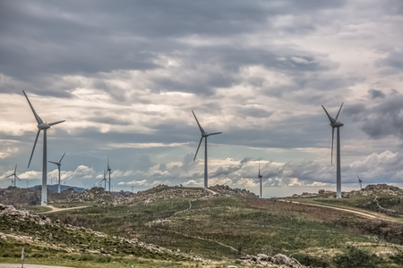 View of a wind turbines on top of mountains, dramatic sky as background, in Portugal Stockfoto
