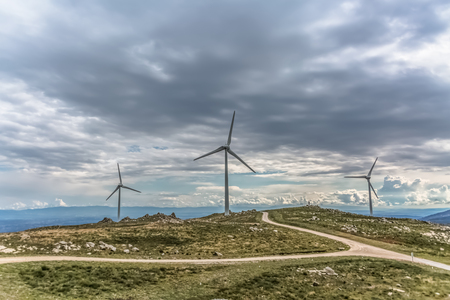 View of a wind turbines on top of mountains, dramatic sky as background, in Portugal Archivio Fotografico
