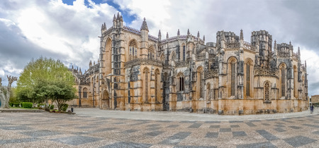 Coimbra / Portugal - 04 04 2019 : View of the ornate Gothic exterior facade of the Monastery of Batalha, Mosteiro da Batalha, literally the Monastery of the Battle, is a Dominican convent, in Leiria, Portugal
