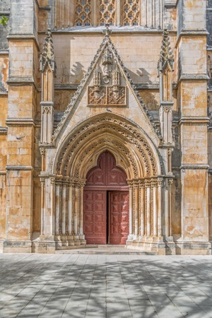 Coimbra / Portugal - 04 04 2019 : Detail view at the frontal gate and door of the ornate Gothic exterior facade of the Monastery of Batalha, Mosteiro da Batalha, literally the Monastery of the Battle, is a Dominican convent, in Leiria, Portugal Stock Photo