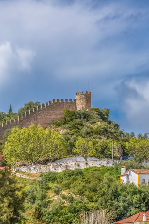 """Obidos / Leiria / Portugal - 04 04 2019 : View of the fortress and Luso Roman castle of Ã""""bidos, with buildings of Portuguese vernacular architecture and sky with clouds, in Portugal"""