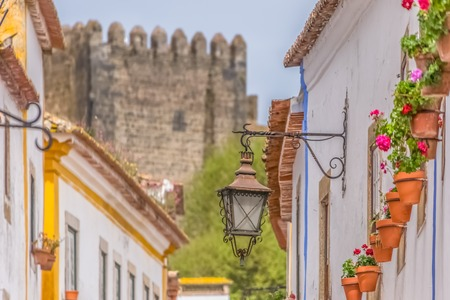 """Obidos  Leiria  Portugal - 04 04 2019 : View of a Portuguese vernacular buildings on medieval village inside the fortress and Luso Roman castle of Ã""""bidos, in Portugal"""