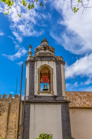"Obidos / Leiria / Portugal - 04 04 2019 : View of a catholic church tower on medieval village inside the fortress and Luso Roman castle of Ã""bidos, in Portugal Standard-Bild"
