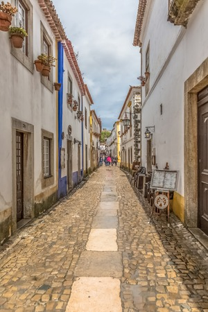 """Obidos / Leiria / Portugal - 04 04 2019 : View of a portuguese street with buildings and tourist people, on Portuguese medieval village of Ã""""bidos, in Portugal"""