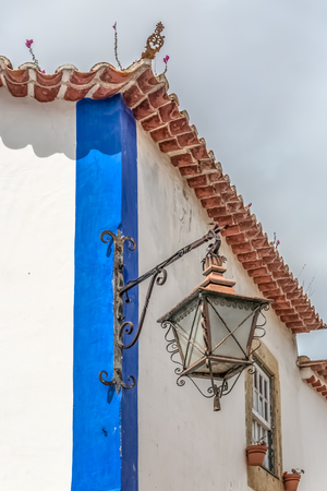 """Obidos  Leiria  Portugal - 04 04 2019 : View of a typical retro street lamp on corner at the traditional building, on medieval village of Ã""""bidos, in Portugal"""