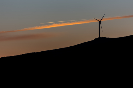 Silhouette view of a wind turbines on top of mountains, sunset sky, in Portugal