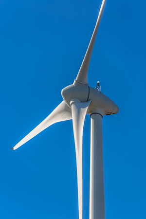 Detailed close up view of a wind turbines; generator, rotor and blade view on blue sky background Фото со стока