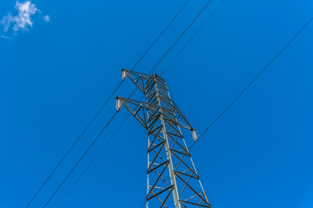 View of metallic structure tower and power lines, blue sky as background